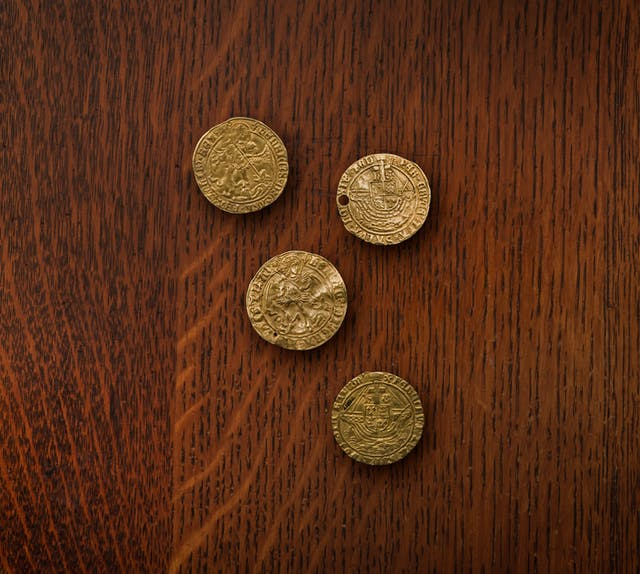 A photograph of four gold coin touch pieces, each coin has markings around its edge and across its face, one of the coins is punctured with a hole.
