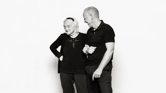 Photographic portrait of an elderly lady linking arms with a male carer against a white background.