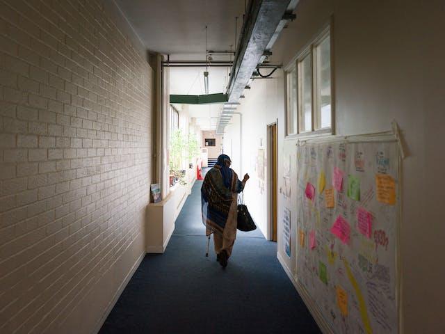 Photograph of Sarifa Patel walking down a corridor.