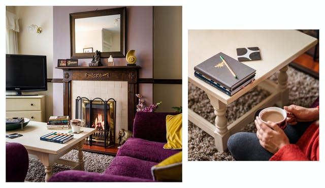 Photographic diptych showing a living room with a fire burning in the fireplace, a sofa, tv and coffee table, on the left and a close-up of hands holding a hot drink with a pen and note pads on a coffee table, on the right.