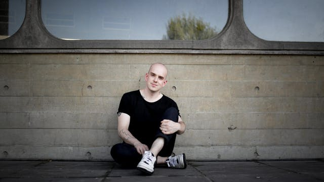 Photograph of a man dressed in black trousers and t-shirt, sitting on the pavement against a concrete wall containing large glass windows.