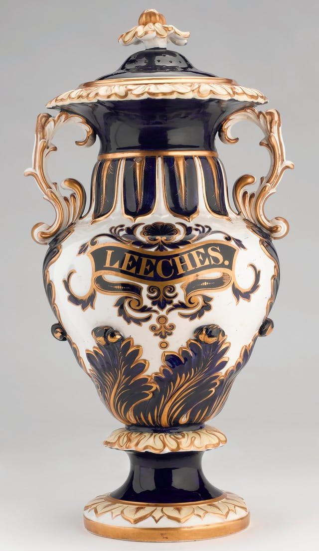 Photo of ornate jar with black, gold and white decoration. In the middle, it says