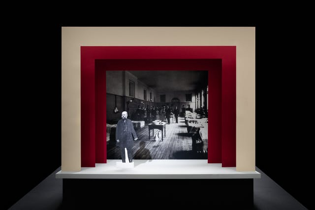 Photograph of a simple theatre stage set, made out of card. The background surrounding the stage is black. The stage floor is white and the framing of the stage is made out of 3 square edged arches, each one smaller than the other, receding backwards. The first arch is cream coloured and the other two are a red. On the stage is a small cut out photograph of a man with a beard from the early 20th century. Behind him forming the backdrop is a black and white archive photograph of a maternity ward, also from the early 20th century.