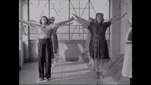 Image of women standing in two lines with their arms stretched upwards.