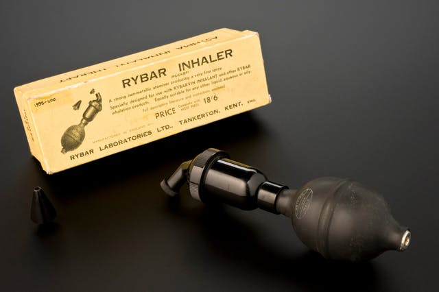 "A ""Rybar Inhaler"" beside the yellowing box it was originally packaged inside. The inhaler has a rubber bulb attached to a metallic-looking tube."