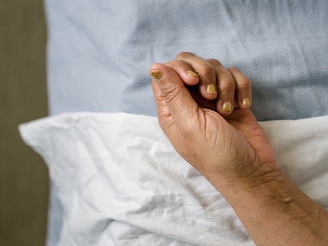 Photograph of the hand of a patient with gold glitter painted fingernails, resting on white and light blue hospital bedsheets.