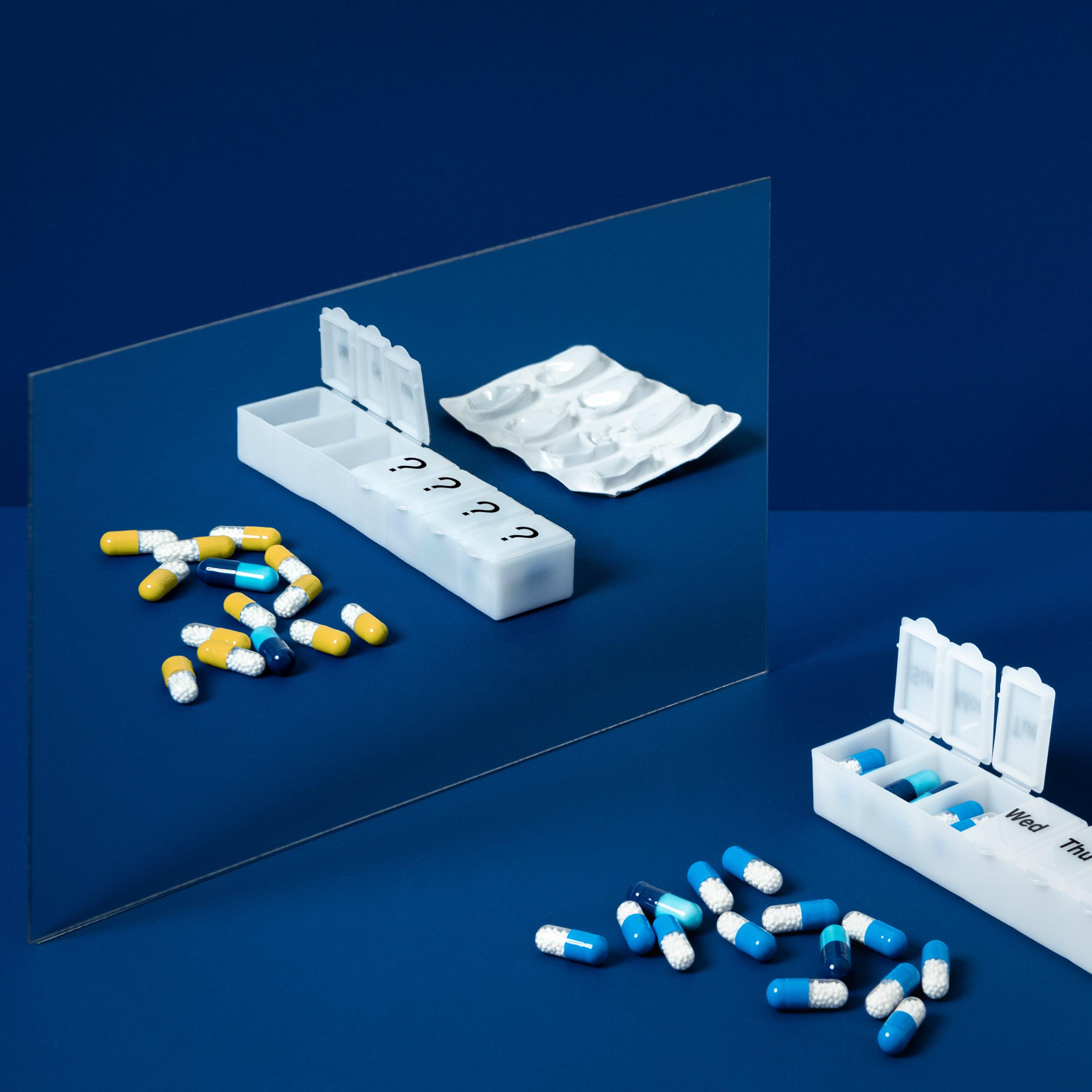 蓝色背景上一面镜子的照片。照片的前景是一个药瓶,上面标有一周的日期,还有一些松散的蓝色和白色药丸。在镜子的映照下,药丸是黄色的。