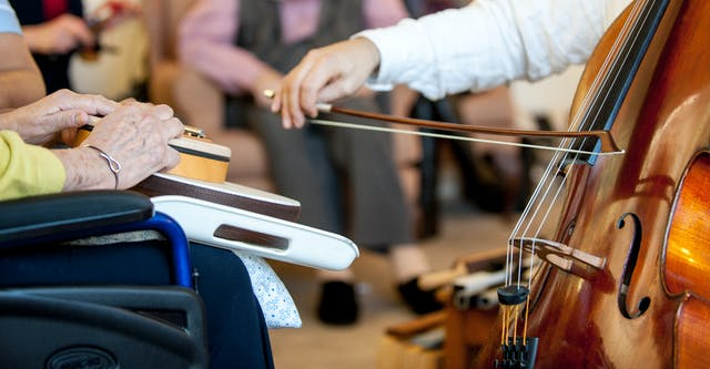 A photograph focusing in on two people sitting opposite each other, showing only their hands. The elderly woman on the left is holding some instruments on her lap, while the person opposite is holding a bow and playing the cello.