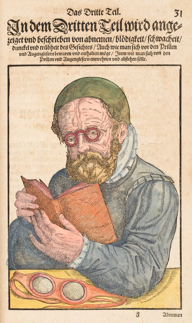 Coloured engraving from a 16th century book showing a man at a table holding an open book in his hands. He is wearing small round glasses. On the table in front of him are a pair red goggles. Above the engraving is ornately written German text.