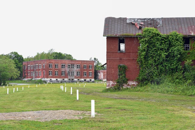 Photograph of two red brick buildings in a state of disrepair, with broken windows and disintegrating roofing materials. On the cut grass next to them are waist high white wooden rectangular posts spread in rough lines across the ground.