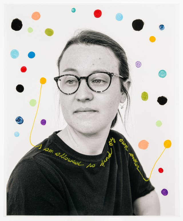 """Head and shoulders photograph of a woman with her body facing to the right of the frame whereas her gaze is off to the left.  A number of colourful dots are hand-drawn over the top of the portrait.  Around the woman's neckline and shoulder the words 'I am allowed to find my own order""""."""
