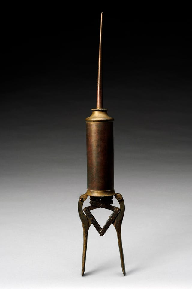 Photograph of a brass enema syringe standing vertically on a background that graduates from white at the bottom of the frame to black at the top.