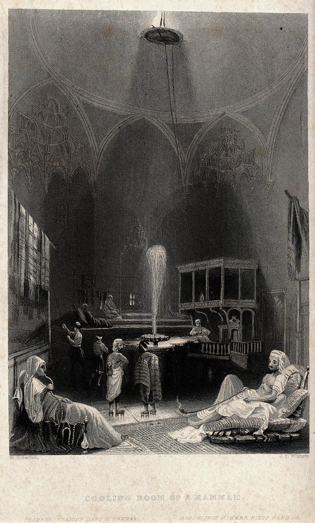 Black and white engraving depicting the cooling room of a hammam, showing people reclining and smoking around a fountain.