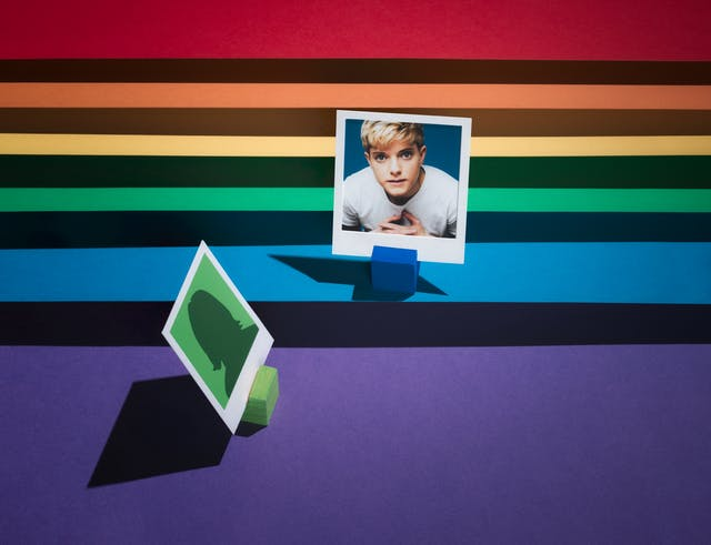 Photograph of a tiered set made up of the LGBTQ+ colours of red, orange, yellow, green, blue and purple.  The tiers form a horizontal line.  On the first tier, the blue one, the portrait of a woman against a blue background is framed in a small white frame.  Below this image, to the left, an anonymous figure on a green background is facing towards her.