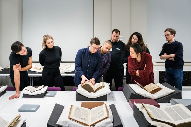 Photograph of a group of people gathered around a large table which is laid out with several old and fragile manuscripts resting on book supports. The person in the centre of the frame is touching one of the manuscripts and appears to be explaining something to the surrounding group.