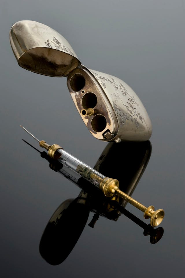 Gold-coloured syringe with a glass tube with measure-lines on, and an engraved rounded metal case similar to a cigarette-case.