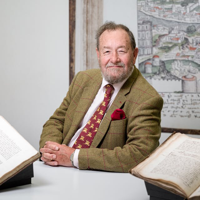 Photographic portrait of Dr Robert Hutchinson in the library at Wellcome Collection. In front of him sits two open manuscripts MS 7117 an English medical compendium c.1575 and MS 375 two surgical treatises of 1506.