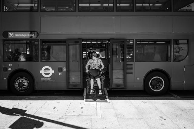 Black and white photograph of an individual reversing their wheelchair onto a London bus.