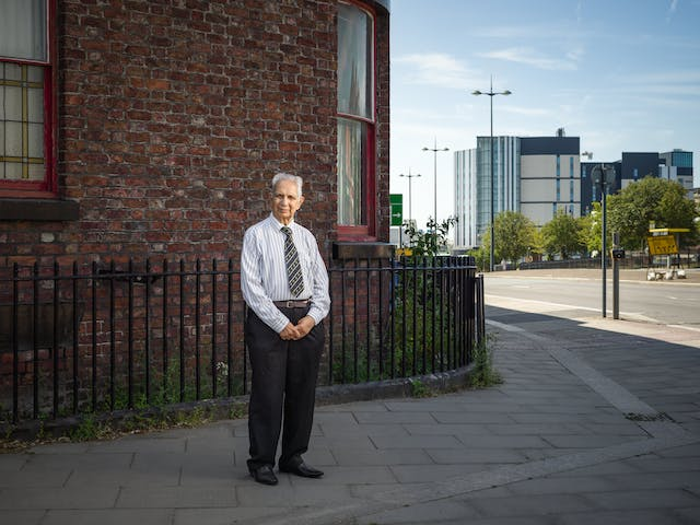 Photographic full length portrait of Dr Shiv Pande, a retires general practitioner, outside his former surgery in Liverpool.