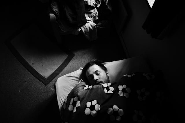 Black and white photograph showing a man lying on a mattress on the floor, his head appearing from a duvet with a football print on it.