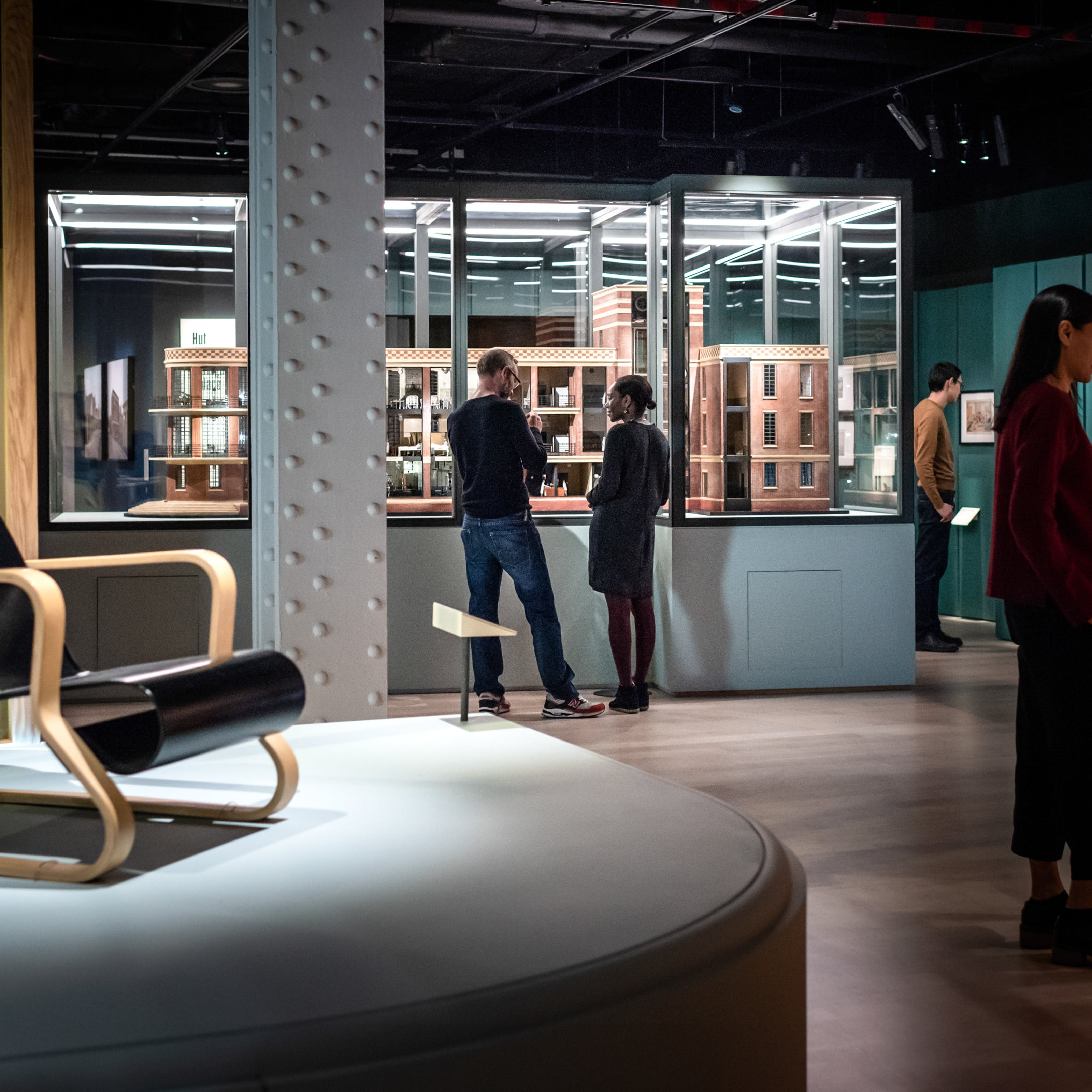 Photograph of visitors exploring the exhibition, Living with Buildings at Wellcome Collection. Photograph shows an architectural model in a display case, an armchair and framed works hanging on the wall.