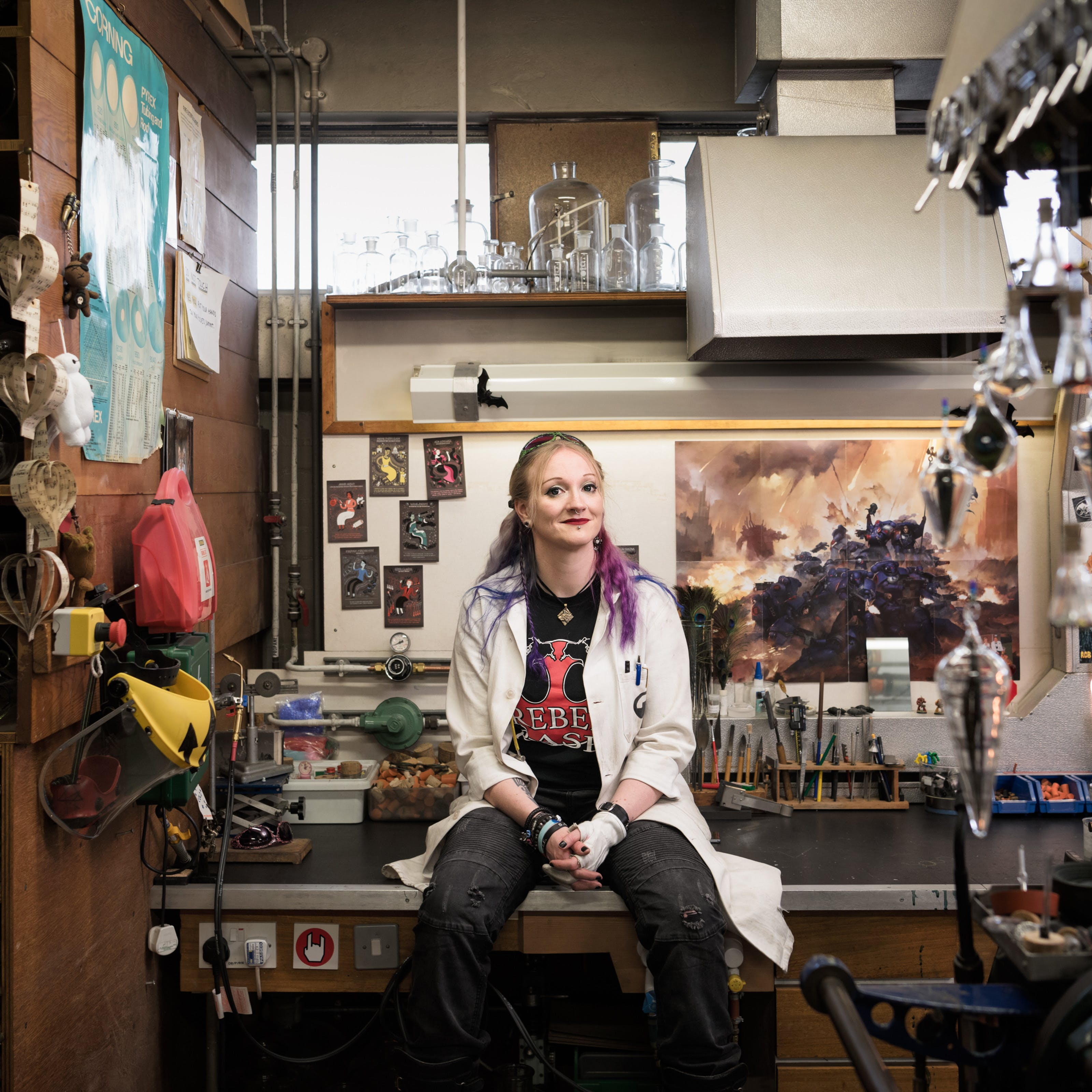 Picture of a woman sitting on a bench in a workshop wearing a white coat, with bright green sunglasses atop her head, blue and purple hair, and a black and red rock-logo t-shirt. Behind her are various glassblowing implements.