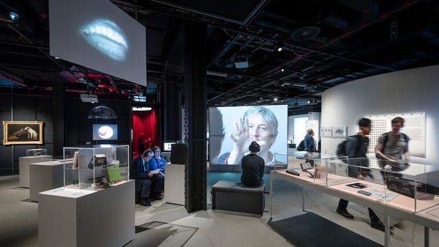 Photograph of visitors exploring the exhibition, This is a Voice at Wellcome Collection.