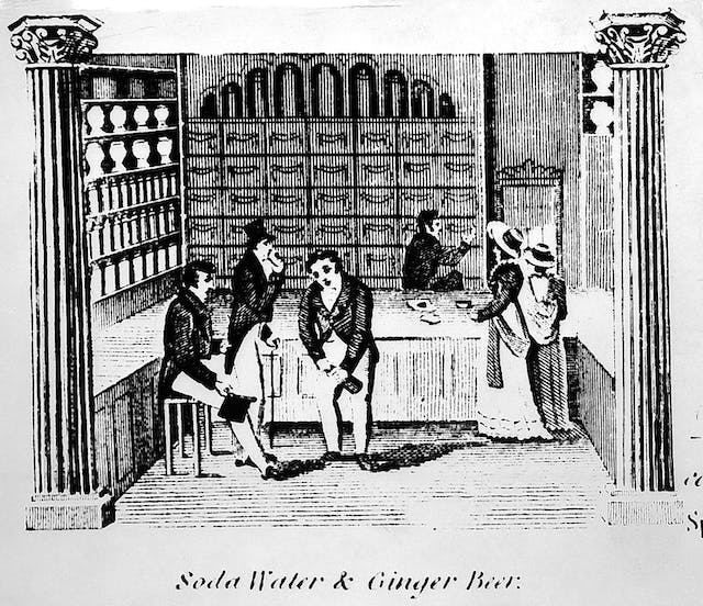 The inside of a pharmacists shop selling soda water and ginger beer. three male customers appear to be drinking whilst two women stand at the counter and a pharmacist in the background reaches for a drawer.