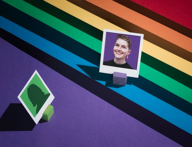 Photograph of a tiered set made up of the LGBTQ+ colours of red, orange, yellow, green, blue and purple.  The tiers form a diagonal line.  On the first tier, the blue one, the portrait of a woman against a purple background is framed in a small white frame.  Below this image, to the left, an anonymous figure on a green background is facing towards her.