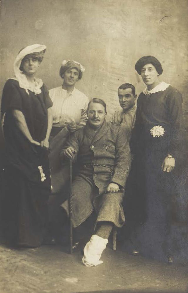 Four soldiers posing, three in drag, with an injured soldier seated in the centre, photographic postcard, c.1910-19