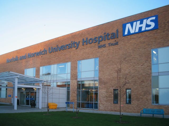 Colour photograph of the entrance to the Arthur South Day Procedure Unit at the Norfolk and Norwich University Hospital. Building is made of brick with large glass windows and a glass entranceway, and has a sign across the top with the name of the hospital trust and with NHS logo.