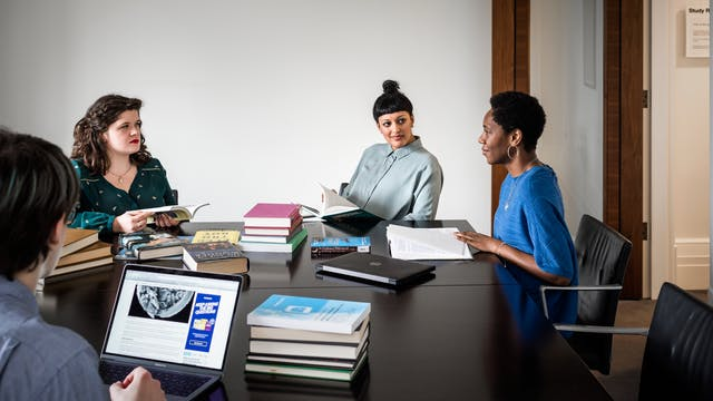 Photograph of four people sat around a large black table in a plain white walled room. In teh background the open wooden door can be seen. On the table are piles of books, a closed laptop computer and an open laptop computer with an website loaded on the screen. The group of people are in a discussion.
