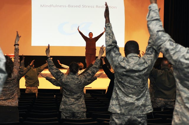 """In front of a screen reading """"Mindfulness-Based Stress Reduction"""", a woman with her arms raised leads a class of people in military fatigues copying her movements."""