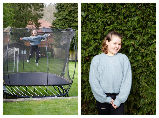 Photographic diptych. The image on the left shows a garden scene with a large trampoline surrounded by grass and trees. On the trampoline is a young girl who has been photographed mid jump, high in the air. She has a broad smile on her face. The image on the right shows the same young girl stood in front of the green foliage of a fir tree, from the waist up. She is smiling and look off to camera right, her fingertips loosely clasps together across the front of her body.