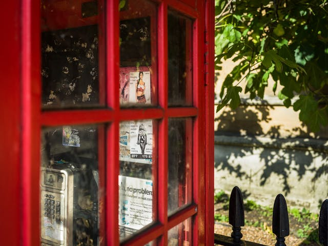 Photograph of a close-up of a red London phone box showing two sex worker advertising cards through the windows in the door.
