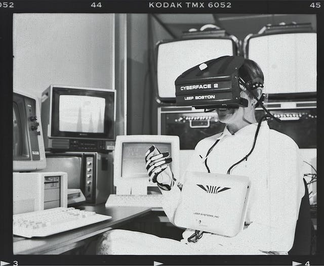 Black and white photograph of a person wearing a large headset labelled Cyberface 2 LEEP Boston, with wires linking to a large rectangular device on their chest and a glove on their right hand. In the background are four chunky 1980s computer monitors and two keyboards.
