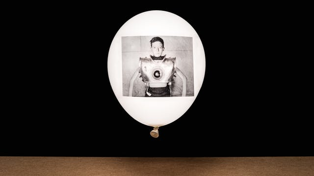 Photograph of a white inflated balloon against a black background, floating vertically above a wooden tabletop horizon line. The balloon looks like it is illuminated from within. On the side of the balloon is a rectangular, monochrome archive film still. The still shows a young boy facing the camera. His chest in encased in large metal contraption which is artificial ventilator.