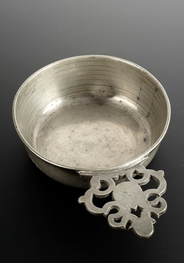 Photo of silver coloured round dish with ornate handle.