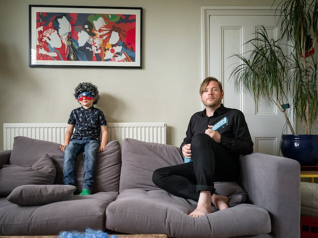 Photograph of a man and his son siting on a sofa in a living room. The son is wearing a grey curly wig and an eye mask made of a red and blue stripe and a single white star. The father is holding a small blue guitar. Behind them on the wall is a colourful poster.