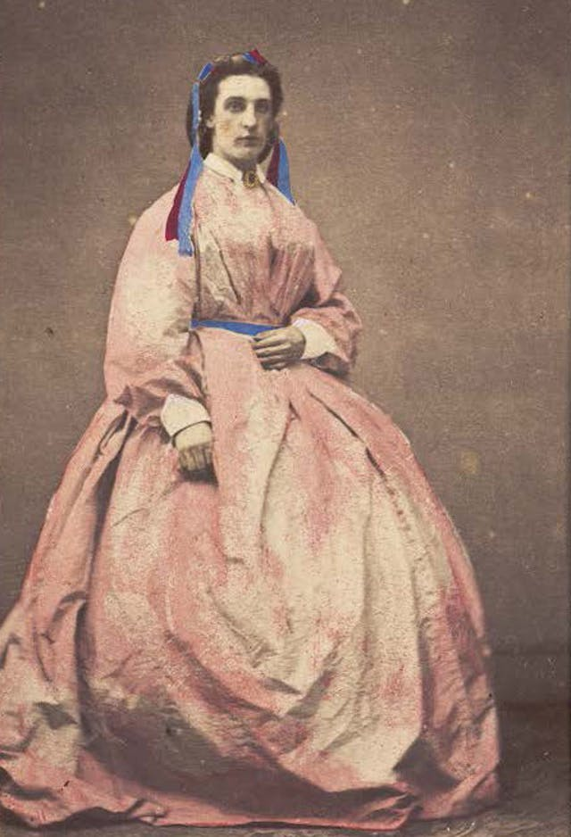 A man in drag poses wearing a large pink dress, photograph, c.1890