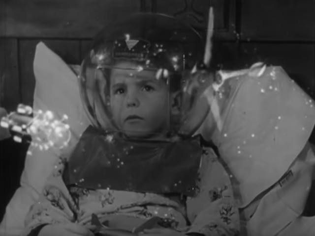 Still from black and white film featuring a boy in bed wearing a space helmet