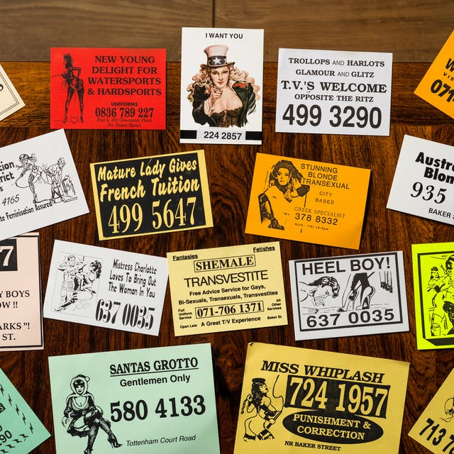 Photograph of a selection of cards from the sex worker card collection at Wellcome Collection, laid out on a wooden tabletop.