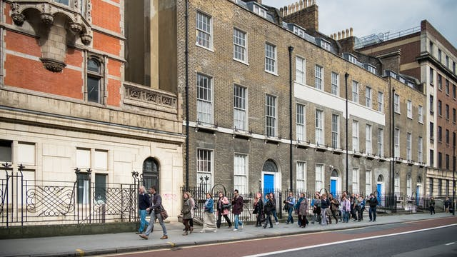 Photograph of a public walking tour on the streets of London showing a line of people walking along the pavement.