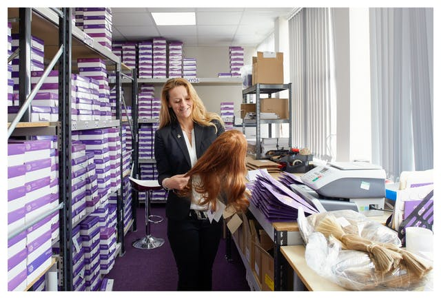 Photograph showing a woman dressed in a white blouse and dark jacket standing in a storeroom. She is looking down at her hands,  in which she is holding a ginger coloured wig. Surrounding her is shelving containing many purple and white boxes stacked on top of one another. To the right is a table top containing a piece of office equipment, purple envelopes and a bag of cut blonde hair.