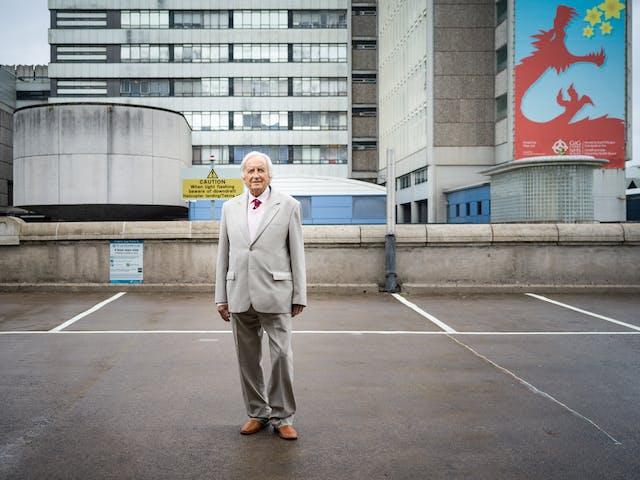 Photographic full length portrait of Morgan David Enoch, psychiatrist, outside the University Hospital of Wales, Cardiff.
