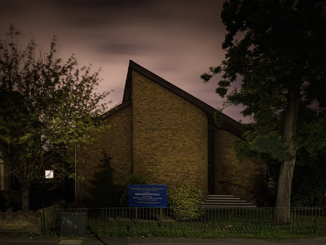 Photograph of Woodford spiritualist church, London at night.  The architecture of the church is such that it the apex of the pitched roof is off centre to the left.  The construction is bare brick with stairs to the entrance on the right.