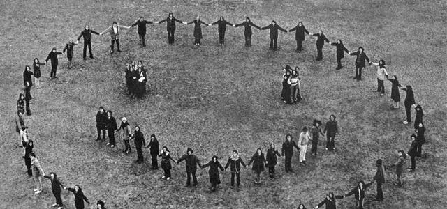 Black and white photograph of a group of people standing in a field, holding hands in a large circle, a smaller semicircle, and two small huddles, thereby forming the outline of a smiling face.