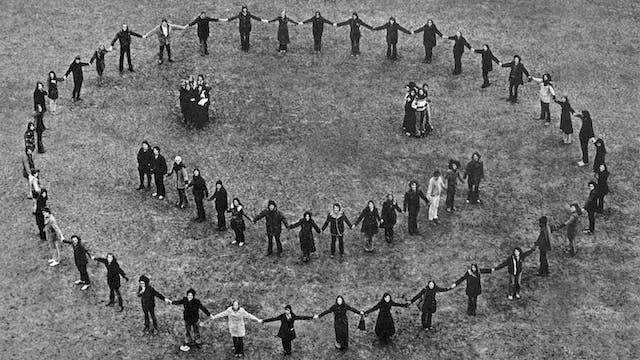 站立在领域的一群人的黑白照片,握在一个大圈子,一个小的半圆形和两个小休碰的手,从而形成一个微笑的面孔的轮廓。