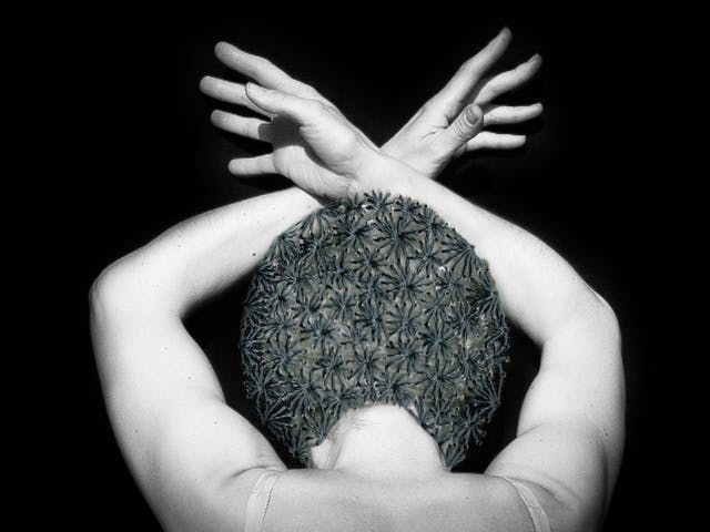 Artwork made up of a black and white photograph of a female figure from behind, against a black background. Her arms are held above her head and her wrists cross, fingers extended. Embroidered into the photographic print with grey thread is a crisscross floral pattern which exactly covers her head and hair.