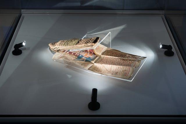 展示玻璃展示案件的照片从15世纪显示一个非常脆弱的折叠的almanac,这部分打开并支持了Perspex Mount。七星队比3个小灯微微射击。它具有织物纹理盖板和折叠的内部页面,这些页面覆盖了手写文本和图表。